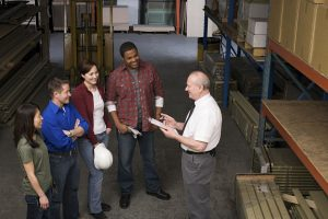 Workers in warehouse talking in a group