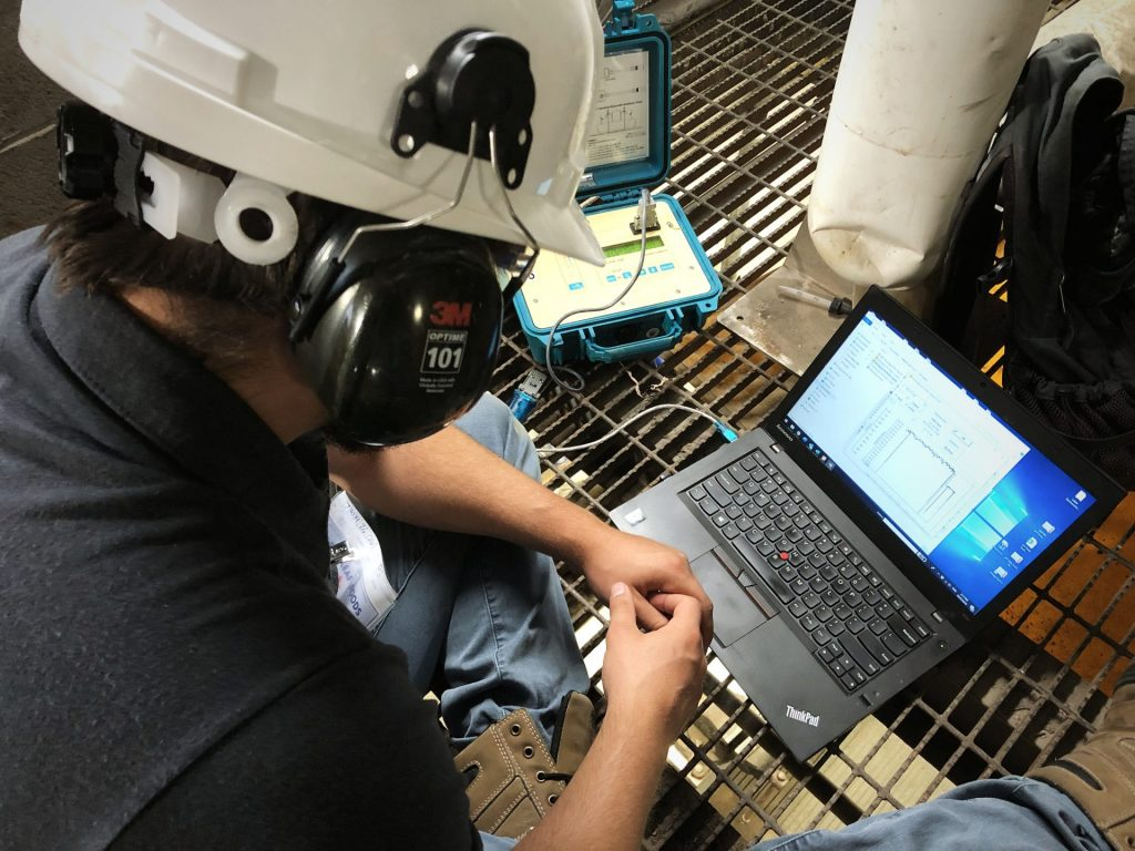 Worker looking at laptop in a factory.